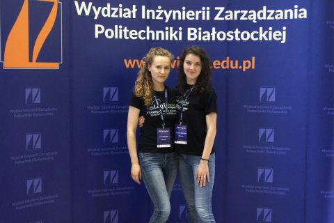Studentki z SKN LogiSQUAD - Julia i Agnieszka na tel ścianki wystawowej WIZ PB